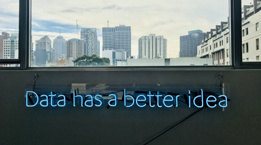 "Neon sign saying ""data is a better idea"" in front of a city skyline"